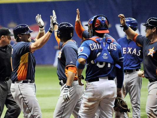 Houston Astros' Jonathan Meyer, left, is congratulated by teammates on his grand slam home run in the fifth inning of a spring exhibition baseball game against the Texas Rangers on Saturday, March 29, 2014, in San Antonio. (AP Photo/Darren Abate)