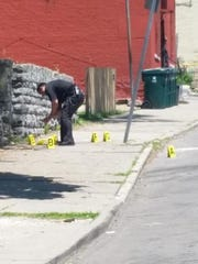 Police examine shell casings at a shooting in the 2300 block of Vine Street.
