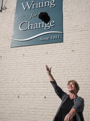 Ann Kult throws her hat up into the air like Mary Tyler Moore outside of the Women Writing for a Change Center on Saturday Feb. 20, 2016 (Phil Didion for The Enquirer).