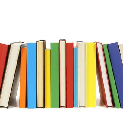 Long row of colorful library books isolated on white background .