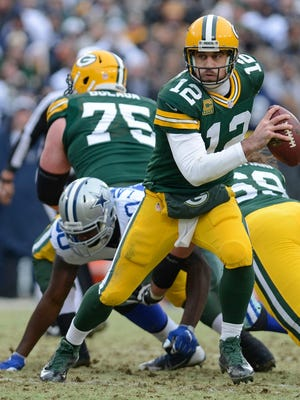 Green Bay Packers quarterback Aaron Rodgers (12) runs out of the pocket in the fourth quarter of Sunday's game against the Dallas Cowboys at Lambeau Field in Green Bay.