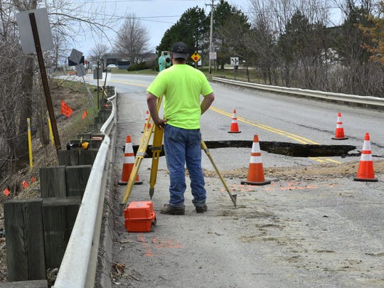 An Engineers Construction Inc. employee surveys on Tuesday, April 11, 2017, the area on the line between Kimball Avenue in South Burlington and Marshall Avenue in Williston where a sinkhole has formed.