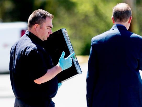 An agent carries an electronic device at the scene