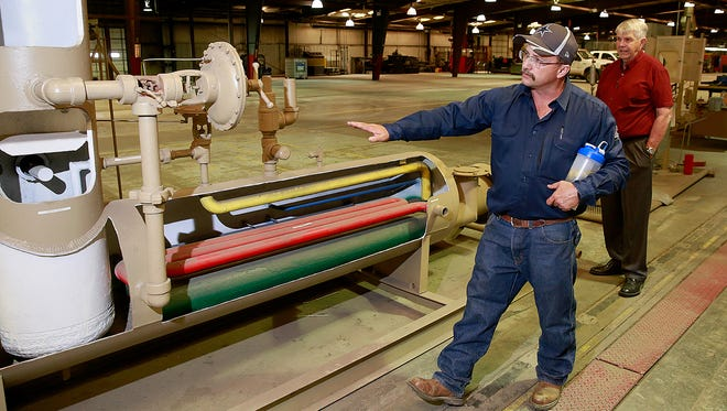 Head mechanic Gary Payne describes the workings of a high-pressure heated separator on Sept. 13 at Dugan Production Corporation in west Farmington. Dugan Vice President John Alexander stands in the background.