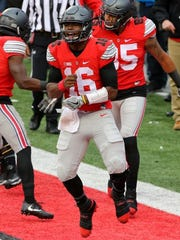 Buckeyes quarterback J.T. Barrett (16) celebrates his touchdown during overtime against the Michigan Wolverines Saturday.