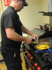 In this News-Messenger file photo, Jim Gippert, owner of Jimmy G's in Fremont, cooks a B3 burger, the smaller version of the restaurant's Goliath burger.