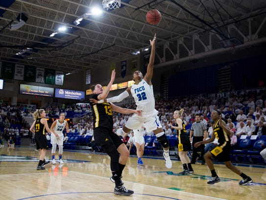FGCU's Rosemarie Julien (32) converts a tough layup against Kennesaw State's Carlotta Gianolla (13)  at Alico Arena on Monday in Fort Myers. FGCU went on to win 78-51 clinching the No. 1 seed in the Atlantic Sun tournament.