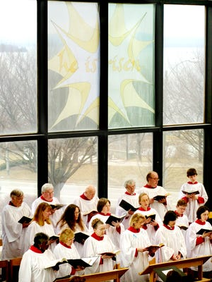 """The St. Paul's Choir sings a hymn beneath a banner reading """"He is risen"""" during a previous Easter service at The Catherdal Church of St. Paul in Burlington."""