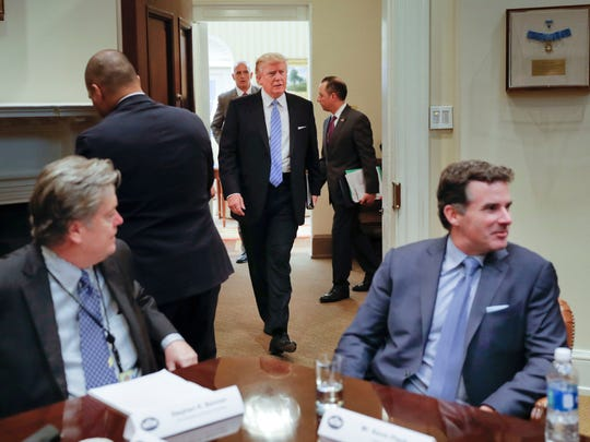 """President Donald Trump walks in from the Oval Office of the White House in Washington in Washington, Monday, Jan. 23, 2017, before hosting breakfast with business leaders in the Roosevelt Room. Sitting at the table is White House Senior Adviser Steve Bannon, left, and Kevin Plank, founder, CEO and Chairman of Under Armour. Plank drew criticism this week when he praised Trump as an """"asset"""" for the country."""