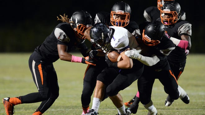 Cocoa defenders (11) Asante Griffin, (21) Marquise Lewis and Taquan Pratt (9) combine for a tackle in a regular season game.