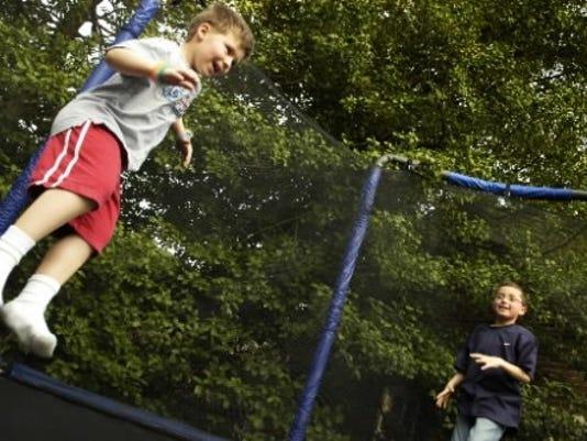 Neighbors Noah Chojnacki, 7, left, and Hunter Wallace, 8, jump on a trampoline in Hunter's backyard (Photo by Kate Penn)