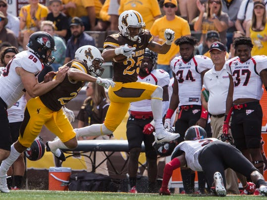 FILE - In this Sept. 9, 2017, file photo, Wyoming wide receiver Austin Conway (25) jumps over Gardner-Webb cornerback Kameron Green (2) during an NCAA college football game, in Laramie, Wyo. At Wyoming, the trade-off the Mountain West is making for television is apparent. The Cowboys drew more fans to Memorial Stadium for afternoon games in September against Gardner-Webb and Texas State than they did for the Mountain West opener against Hawaii, which kicked off at 8:15 p.m. Mountain time.(Josh Galemore/The Casper Star-Tribune via AP)/The Casper Star-Tribune via AP)