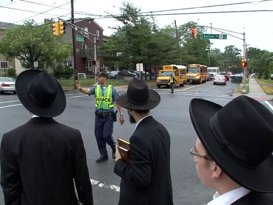 Orthodox men wait in June to cross 9th Street at Route 9 in Lakewood.