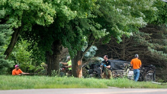 A group of men tries to untangle branches from the wreckage of a single-vehicle accident Monday southwest of Bartonville. A woman in her 40s was killed, and two others were injured.