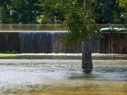 Water flows over the top of levee on River Road as the Vermilion River continues to rise.