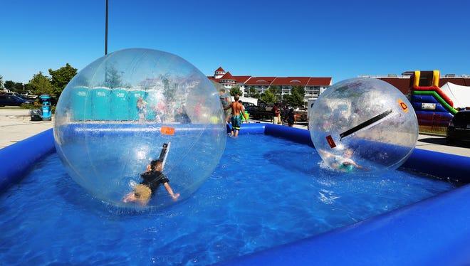 Children enjoy the water ball amusement at Lakeshore Weekend at south pier Saturday July 29, 2017 in Sheboygan, Wis.