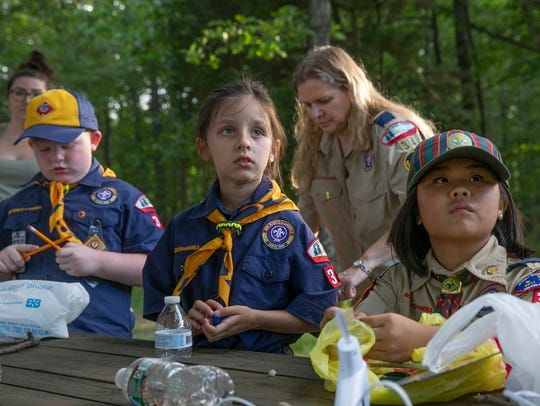 Lorelei Forman, 7, and Luci Juchniewicz, 10, listen to instructions as the Cub Scouts build their boats for Jackson Pack 34's Raingutter Regatta.