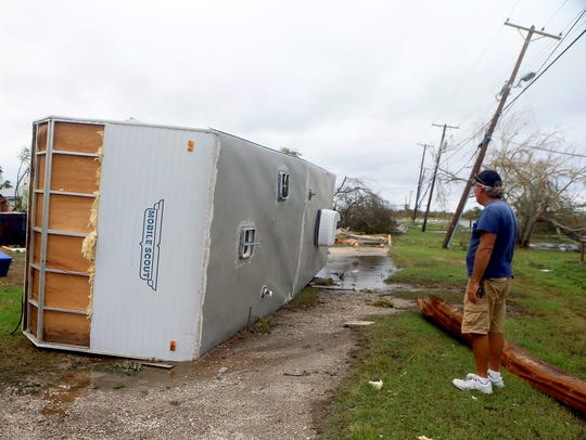 Terry Duncan views his mobile home after it flipped