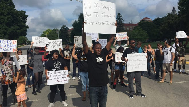 Brandon Allen, center, a Purdue graduate student, leads a group to block State Street on Friday morning in a Black Lives Matter rally.