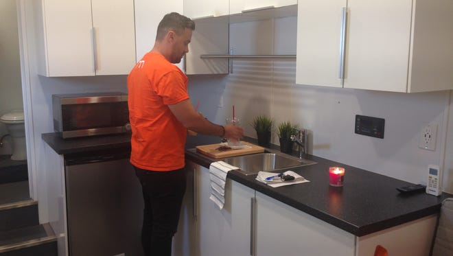 """Modern Container Concepts co-founder Adrian Garneata in the """"Relief Box"""" kitchen."""