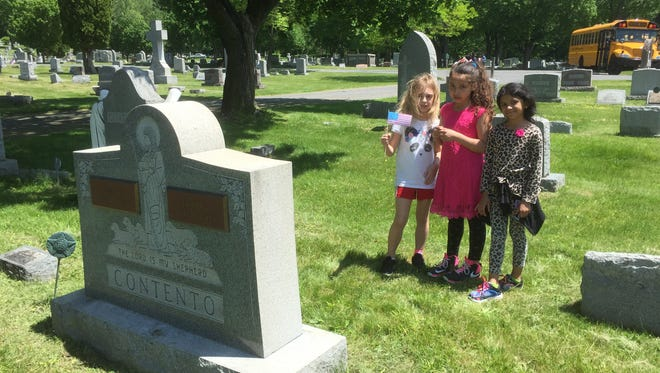 Johnson City Central School District third-graders learned cemetery etiquette while placing flags next to the graves of veterans in Calvary Cemetery.