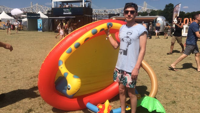 Alex Kuball stands with his inflatable pool hefted over one shoulder as he heads toward the Mast Stage at Forecastle. July 16, 2017