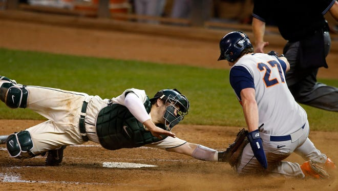 Michigan State catcher Chad Roskelly, left, tags out Illinois designated hitter Pat McInerney (27) who trying to get home from second base on a single in the eighth inning of a third-round NCAA Big Ten tournament college baseball game Friday, May 22, 2015, in Minneapolis.