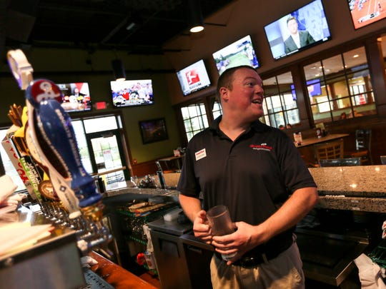 Jordan Whaley, a 33-year-old assistant manager for Grotto Pizza in Middletown, pours a beer for a customer.