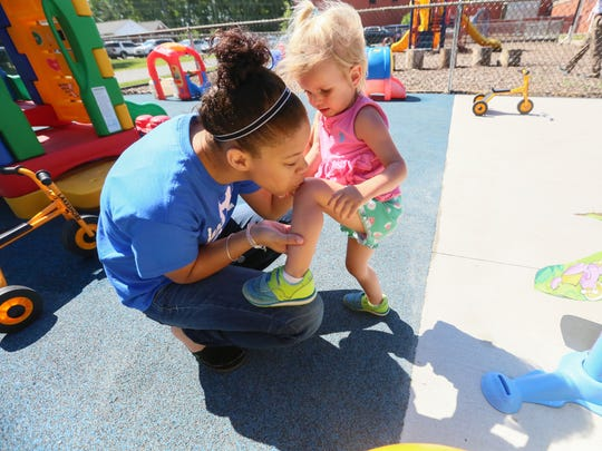 Raelynn Jackson, an intern at Parents and Children Together at Tech United Cerebral Palsy of Delaware child care center at Sussex Technical High School, gives 2 year-old Laine Hade a kiss on her knee after she bumped it on the playground.