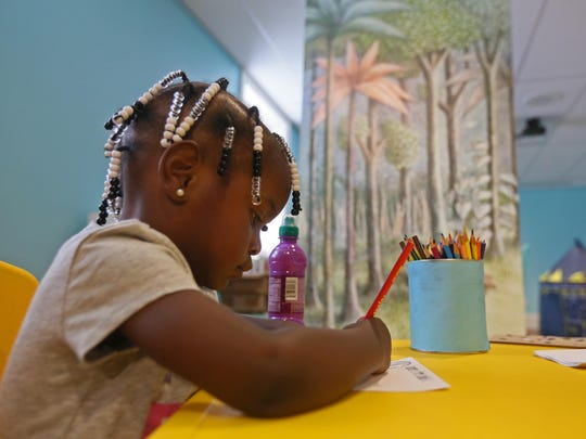 """Arian Knight, 2, colors in the """"Land of the Wild Things"""" room, which was created for children to make art after seeing an exhibit with author and illustrator Maurice Sendak's work from his famed children's book """"Where the Wild Things Are"""" at the Biggs Museum of American Art in Dover."""