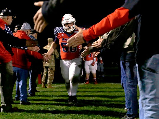 """Lincoln's Austin Reimer high-fives military members and veterans as the team takes the field before the """"Raiders Salute"""" football game between Lincoln and D.C. Everest on Friday in Wisconsin Rapids."""