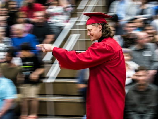 A graduate points to the crowd while walking into the