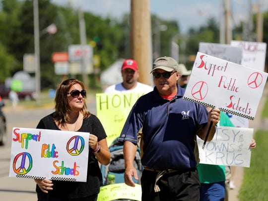Protesters Jennie Moore and Andy Kloff walk along North Main Street in front of Adams-Friendship Middle School in Adams, Wisconsin, as U.S. Secretary of Education Betsy DeVos makes a stop at the school Tuesday, July 24, 2018.
