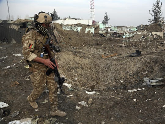 In this Nov. 29, 2018, file photo a Afghan Security forces member walks next to a crater caused by suicide bomb attack in Kabul, Afghanistan.