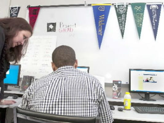Robyn Meadows, the campus coordinator for Project Grad at William Penn High School, helps out senior Freddy Desantis.