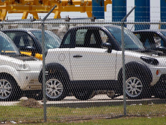 In this June 13, 2016 photo production cars are parked outside the GreenTech Automotive manufacturing plant in Robinsonville, Miss.