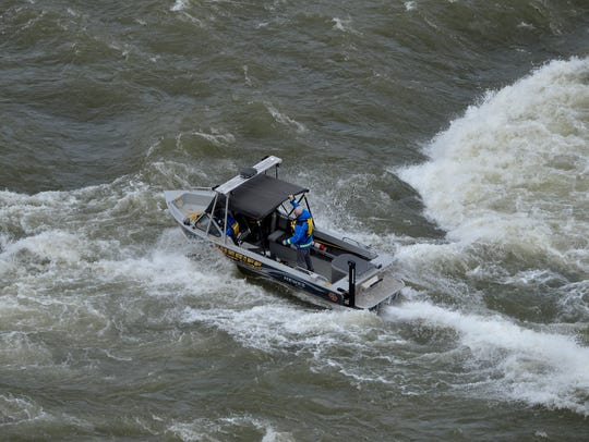 A boat from the Cascade County Sheriff's Office makes its way through rough waters to Black Eagle Falls on the Missouri River to search for a woman, later identified as Brittney Roberts, who was washed over the Black Eagle Dam.