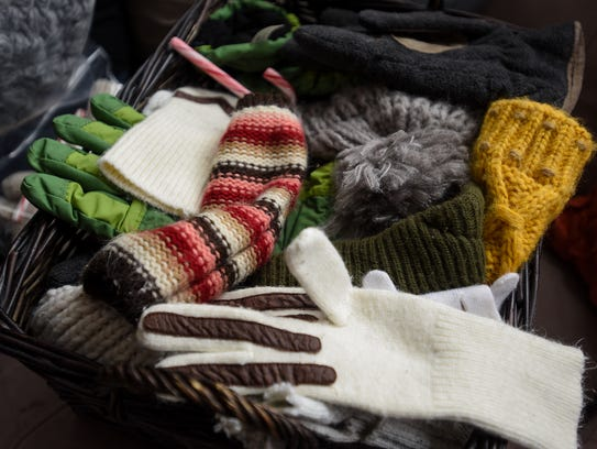 Donated scarves, hats and gloves in a basket will be