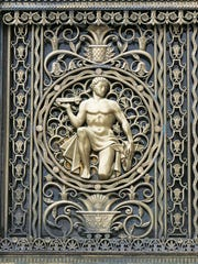 A figure holding an automobile is part of the bronze decorative grill work seen above the West Grand Boulevard entrance on the exterior of the Fisher Building in Detroit. This is the work of Geza R. Maroti.