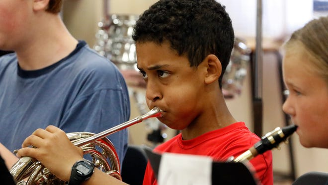 File - 2016 Summer Band Bash student Sam Pribyl performs with the French horn during a rehearsal at Washington Junior High School.