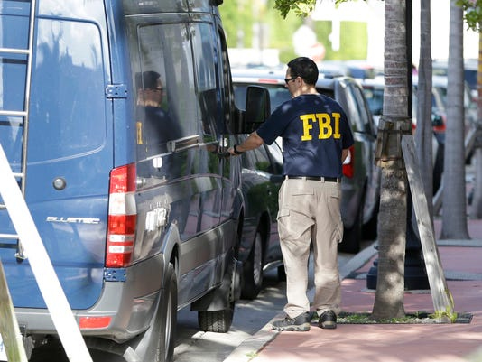 "An FBI agent retrieves equipment from a van as he prepares to re-enter the offices of the Confederation of North, Central America and Caribbean Association Football (CONCACAF,) Wednesday, May 27, 2015, in Miami Beach, Fla. Swiss prosecutors opened criminal proceedings into FIFA's awarding of the 2018 and 2022 World Cups, only hours after seven soccer officials were arrested Wednesday pending extradition to the U.S. in a separate probe of ""rampant, systemic, and deep-rooted"" corruption. (AP Photo/Wilfredo Lee)"