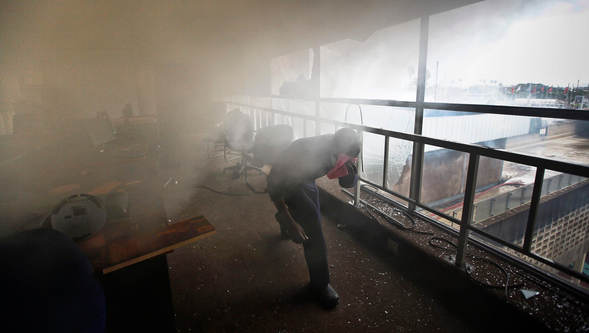 A police officer avoids smoke as he helps firefighters put out a fire at Jomo Kenyatta International Airport. There were no injuries reported.