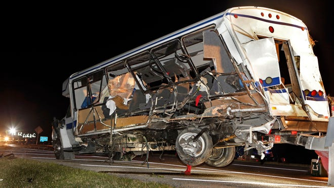 A wrecker removes the North Central Texas softball team bus as Highway Patrol and emergency personnel work the scene of a fatal accident in Oklahoma.