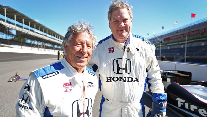 IndyCar racer Mario Andretti, left, poses for a photo with Indianapolis Star reporter John Tuohy after driving him in a two-seater at the Indianapolis Motor Speedway, Wednesday, May 13, 2015.