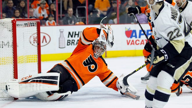 Steve Mason's save on Pittsburgh Penguins' Kael Mouillerat, right, helped propel the team into the playoffs.