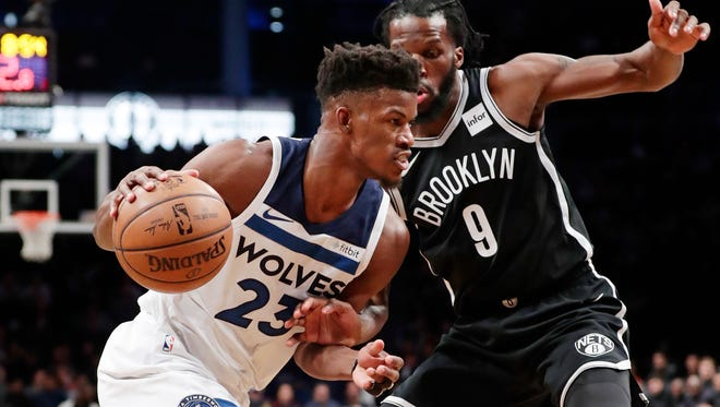 Minnesota Timberwolves' Jimmy Butler (23) drives past Brooklyn Nets' DeMarre Carroll (9) during the first half of an NBA basketball game Wednesday, Jan. 3, 2018, in New York. (AP Photo/Frank Franklin II)