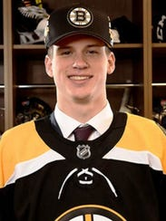 Jack Studnicka tries on his Boston Bruins hat and jersey