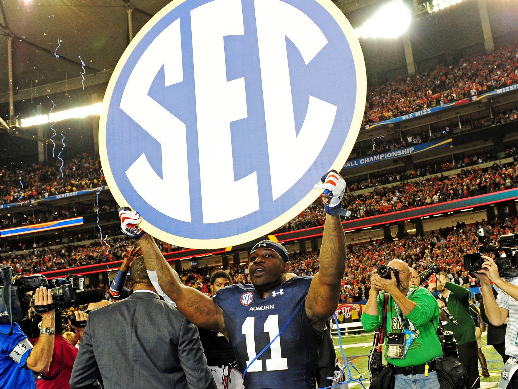 Auburn cornerback Chris Davis holds up the SEC sign after the 2013 SEC Championship game against Missouri.