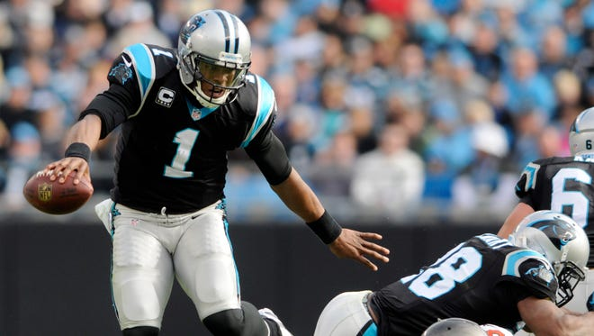Carolina Panthers' Cam Newton (1) dodges Tampa Bay Buccaneers' Mason Foster (59) in the first half of an NFL football game in Charlotte, N.C., Sunday, Dec. 1, 2013. (AP Photo/Mike McCarn)