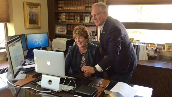 Jean Branscum, chief executive officer of the Montana Medical Association, gets some help a few years ago from Attorney General Tim Fox in taking the Pledge to End Prescription Drug Abuse in Montana.